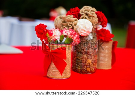 Decorations and decor of red and white wedding flowers at a reception event. - stock photo