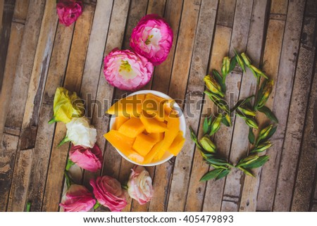 decorations for March 8 Women's Day celebration , flowers buds eustomy number 8 written on wooden brown rustic Josquin in stie, a plate of ripe mango
