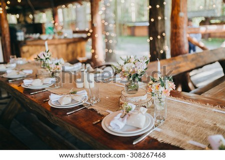 decorations made of wood and wildflowers served on the festive table - stock photo