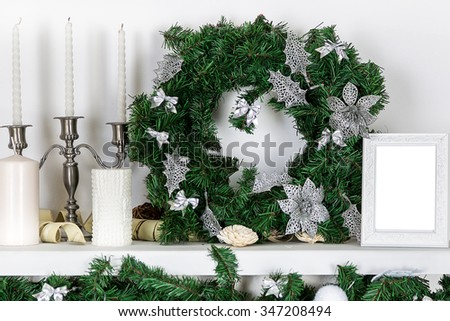 Decorations on the Christmas fireplace in the form of candlesticks, Christmas wreath and photo frames - stock photo