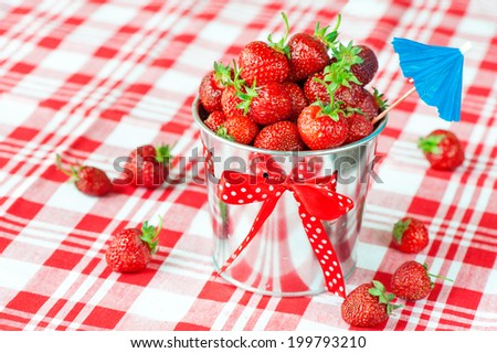 Decorative aluminium pail full of generous crop of ripe fresh juicy gourmet red summer strawberry. Indoors close-up. - stock photo