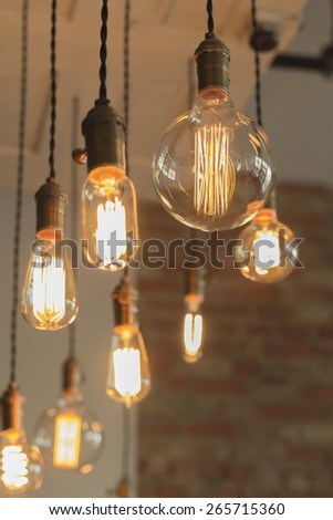Decorative antique edison style light bulbs against brick wall background - stock photo