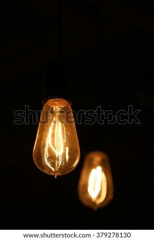 Decorative antique edison style light bulbs against dark background - stock photo