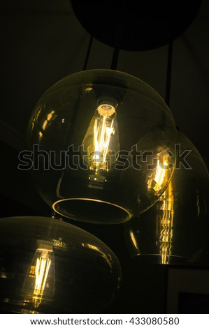 Decorative antique edison style light bulbs chandelier background - stock photo