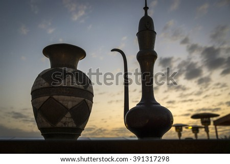 Decorative Arabian vase and jug pictured at sunset in the desert near Dubai, in the United Arab Emirates  - stock photo
