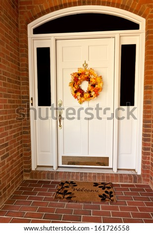 Decorative autumn wreath on a white front door - stock photo