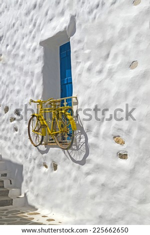 Decorative bicycle hanging from a window in a Greek house on Naxos island, Greece - stock photo