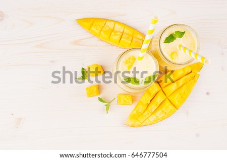 Decorative border of yellow mango fruit smoothie in glass jars with straw, mint leaves, mango slices, top view. White wooden board background, copy space.