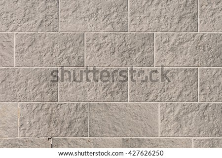 Decorative brick facing. Brick masonry wall or foundation of the house. Texture stacked rough brown and gray bricks. Background stone wall or floor. - stock photo