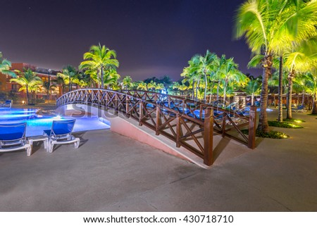 Decorative bridge over swimming pool at a luxury caribbean, tropical resort at night, dawn time.