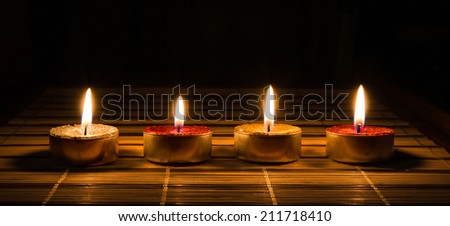 decorative candles burning on the table in the dark