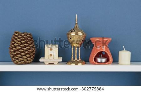 Decorative candles on white  shelf on blue wallpaper background - stock photo