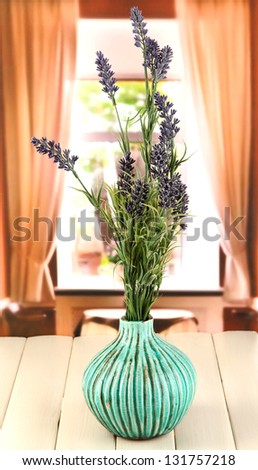 Decorative ceramic vase with lavender on wooden table on window background