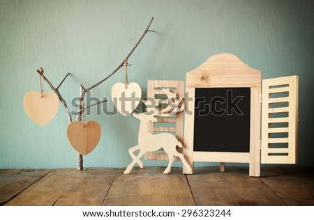 decorative chalkboard frame and wooden hanging hearts over wooden table. ready for text or mockup. retro filtered image - stock photo