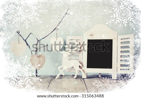 decorative chalkboard frame and wooden hanging hearts over wooden table. ready for text or mockup. retro filtered image with snowflake overlay  - stock photo