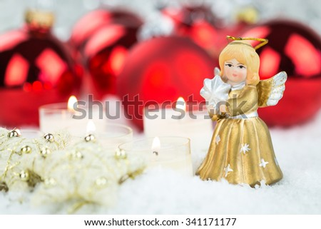 Decorative Christmas arrangement with red shiny baubles, burning white candles and handmade stars near a vintage golden angel figurine, on white snow