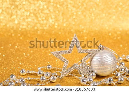 Decorative christmas ball and beads on golden glitter background