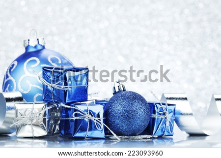 Decorative Christmas balls and gifts on silver bokeh background - stock photo
