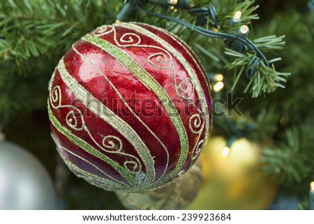 Decorative Christmas bulb hanging on a faux pine tree in anticipation of the December holiday. - stock photo