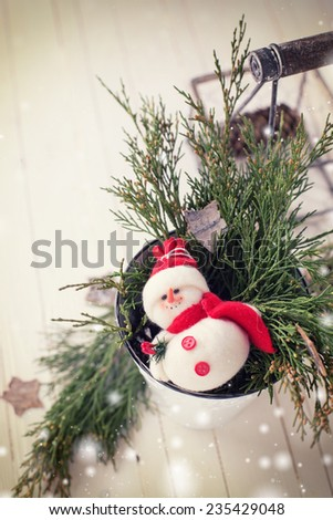 Decorative christmas composition -  spruce,  little snowman in white pot on wooden background. Copy space  for text. Selective focus. - stock photo