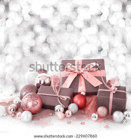 Decorative Christmas gift arrangement with gift-wrapped boxes tied with salmon pink ribbon amongst Xmas baubles on a background bokeh of falling snow with copyspace for your seasonal greeting - stock photo