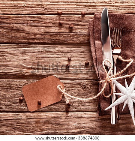 Decorative Christmas place setting on a rustic wood table with cutlery and a brown napkin tied with string and a gift tag with a white star decoration on top, copyspace - stock photo