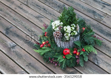 Decorative christmas wreath and flowers in spruce stump, vintage