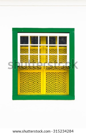 Decorative, colonial, green yellow, vintage, window on a white wall in Paraty or Parati, Brazil. - stock photo