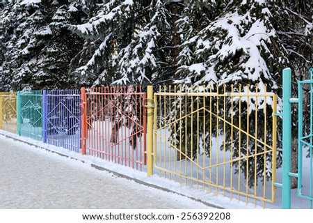 Decorative colored fence. Winter day. Metal, wrought. - stock photo