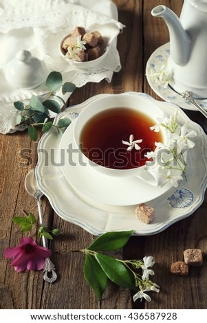 Decorative composition of vintage style: romantic tea drinking with jasmine tea. Toned image - stock photo