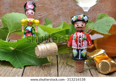 Decorative corkscrew, wine bottle and glass of wine on the wooden table with green twigs vine - stock photo