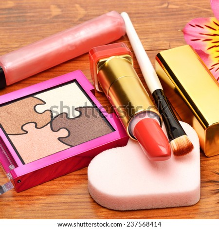 Decorative cosmetics, make-up, eyeshadow, applicator, lipstik, and orchid flower on wooden background - stock photo
