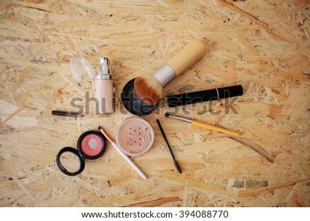 Decorative cosmetics on wooden background. Makeup. Brushes, powder, blush, mascara and pencil.