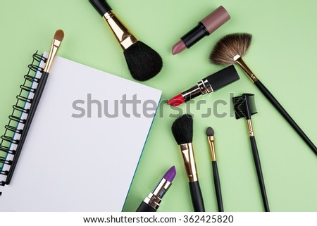 decorative cosmetics with notebook on green background