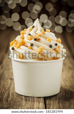 Decorative creamy party vanilla ice cream sundae twirled in a takeaway plastic tub and sprinkled with chocolate pearls and nuts with a background bokeh of party lights - stock photo