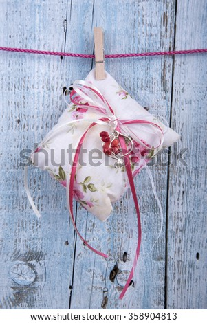 Decorative cushion with ribbons hanging on clothesline on old wooden background
