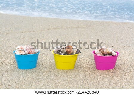 Decorative Easter egg baskets on the beach along the waters edge filled with seashells for use as a background.  - stock photo