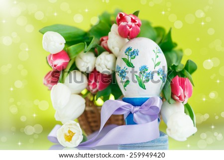 Decorative easter egg with a bouquet of spring tulips on a green background - stock photo
