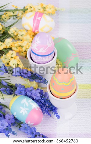Decorative Easter eggs and egg cups with flowers - stock photo