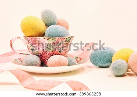 Decorative easter eggs in china tea cup - stock photo