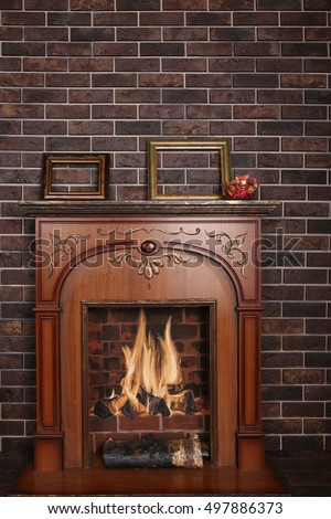 Decorative fireplace in the room on a dark brick background