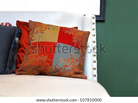 Decorative floral pattern pillow on white chair - stock photo