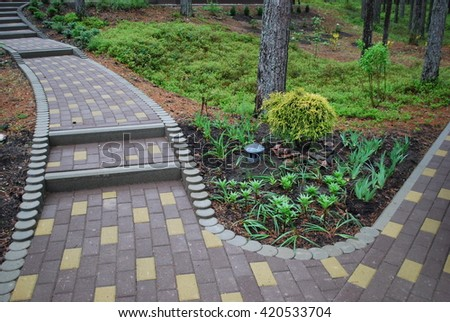 Decorative flower bed with lilies and irises, Chamaecyparis pisifera 'Filifera Aurea' in the center. Stairs of stone blocks. Landscaping.
