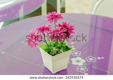 Decorative flower on glass table at Cafe. - stock photo