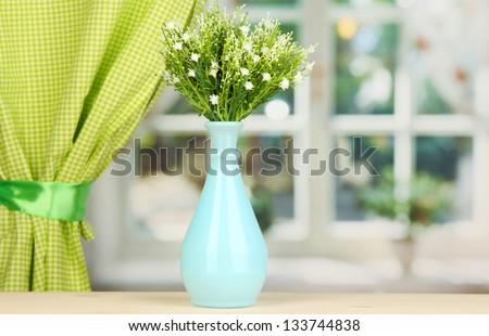Decorative flowers in vase on windowsill - stock photo