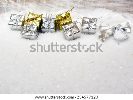 Decorative  gift boxes  in fresh snow against a background bokeh of twinkling party lights  - stock photo
