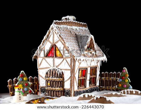 Decorative gingerbread house with lights inside on black background. Rural Christmas night scene - stock photo