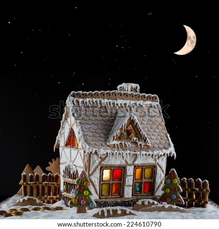 Decorative gingerbread house with lights inside on black background with moon and stars . Rural Christmas night scene - stock photo