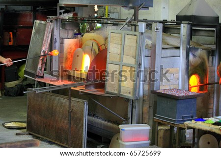Decorative glass being manufactured at Murano, Venice, Italy. A glassma\ker is removing a blob of molten glass on a the end blowpipe from the furnace - stock photo