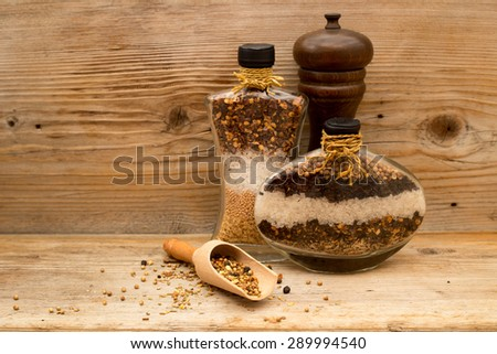 Decorative glass bottles filled with layers of natural spices, red chili peppers, clove, coriander, cumin, mustard seed, fennel, salt; brown wooden spices mill; small scoop on rustic wooden background